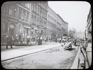 Laborers pave a street, location unknown