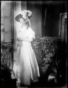 Profile of woman in gown and plumed hat standing with plants