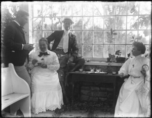 Two men and two women drinking tea in greenhouse