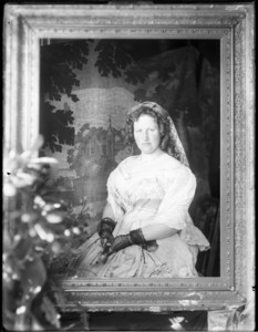 Portrait of woman seated behind empty frame holding fan