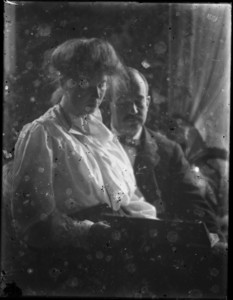 Woman seated on man's lap, holding book