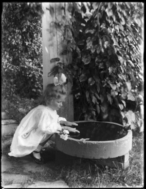 Young girl crouching by bird bath