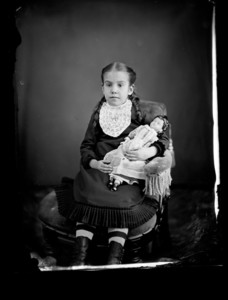 Portrait of a child seated with a doll