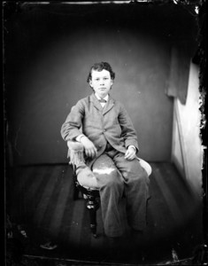 Full portrait of a boy, seated in a chair