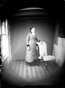 Full length portrait of a woman standing next to a chair