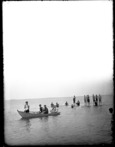 People in a boat and standing in the water at low tide