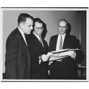 Thomas E. Leggat, standing in the middle, examines an illustrative site plan with two unidentified men
