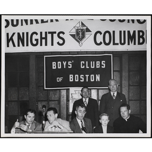 An award winner posing with several officers and guests during an awards event held by the Boys' Clubs of Boston and the Knights of Columbus Bunker Hill Council