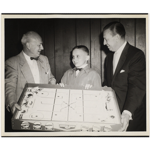 Arthur T. Burger, at left, and Boone Gross presenting an air hockey table to Michael Sarson at a Boys' Clubs of Boston Awards Night