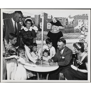 """""""Arthur Curren, Jr., President of Boston Rotary Club and Mrs. Curren signing up Boys' Club Day Campers for the 'Little Sister Contest' while judges Mr. and Mrs. Forrester A. Clark (Pres. of Boys' Club of Boston) and Carole Bridge (Allen Model Agency) look on"""""""