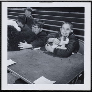 A boy sitting with his cat in his arms while another holds his dog during a Boys' Club Pet Show