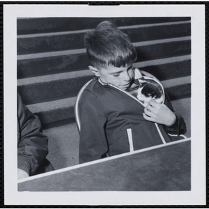 A boy sitting with his cat in his jacket in a Boys' Club Pet Show