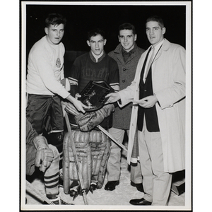 Four men posing on the ice with a plaque at the Boys' Clubs of Boston Hockey League Championship