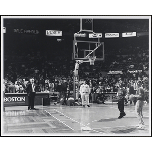 Boston radio personality Dale Arnold, at far right, turns his back with a basketball before throwing it, while the spectators look on, at a fund-raising event held by the Boys and Girls Clubs of Boston and Boston Celtics