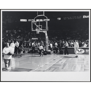 Boston radio personality Andy Moes, at far left, turns his back with a basketball before throwing it, while the spectators look on, at a fund-raising event held by the Boys and Girls Clubs of Boston and Boston Celtics