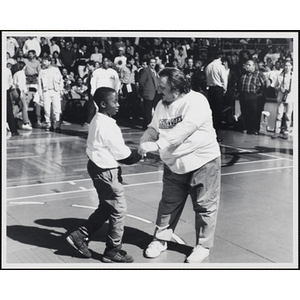 Boston radio personality Andy Moes shakes hands with a boy on a basketball court, while the spectators look on, at a fund-raising event held by the Boys and Girls Clubs of Boston and Boston Celtics
