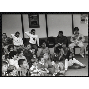 About twenty Boys and Girls Club members looking intently at something while sitting in a room