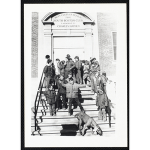 About fifteen Boys & Girls Club members stand on the front steps of the South Boston Clubhouse while a dog goes down the steps in the foreground