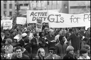 Anti-war protesters marching at the Counter-inaugural demonstrations, 1969, with banners and signs: 'GI's for Peace,' 'Beatle Power,' 'Active duty GIs,' and 'To rebel is justified'