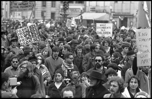 Anti-war protesters marching in the streets at the Counter-inaugural demonstrations, 1969, with banners and signs: 'Promises promises,' 'End racism,' and 'While government talk, children die'