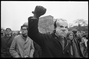 Anti-Vietnam War protester in a paper mache Nixon mask, raising his fist, during the Counter-inaugural demonstrations, 1969