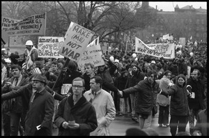 Anti-war protesters marching at the Counter-inaugural demonstrations, 1969, with banners and signs: 'Make me, not war'