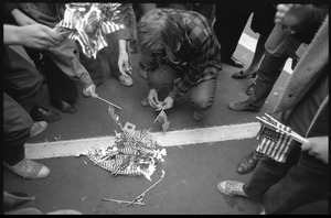 Anti-Vietnam War protesters kneeling on the ground, preparing to burn miniature American flags distributed by the Boy Scouts during the Counter-inaugural demonstrations, 1969