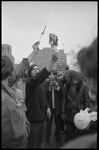 Anti-Vietnam War protesters hold up a burning clutch of miniature American flags distributed by the Boy Scouts during the Counter-inaugural demonstrations, 1969
