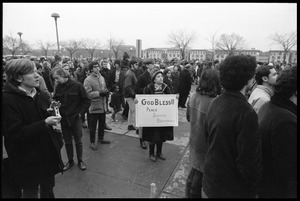Anti-Vietnam War marchers, one older woman holding a sign reading 'God Bless Peace, Justice, Brotherhood': during the Counter-inaugural demonstrations, 1969