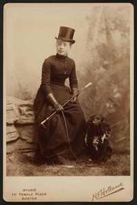 Full-length portrait of Lesley Dillingham Bangs, seated on a studio prop, facing front, holding a riding crop and her dog's leash, Boston, Mass., 1889
