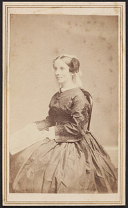 Half-length portrait of Mary Perkins Olmsted, facing three-quarters to the left, seated on a chair, holding papers, location unknown, 1863