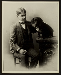 Three-quarter length portrait of Gardner Richardson, seated, facing front with his dog, location unknown
