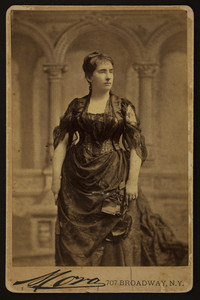 Three-quarter length portrait of Mary Bowen Holt, standing, facing right, Mora, 707 Broadway, New York, New York