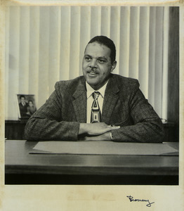 Randolph W. Bromery sitting indoors, behind desk