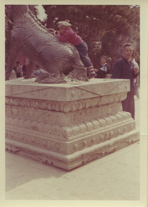 Child climbing on a bronze qilin at the Summer Palace in Beijing, China