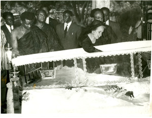 Shirley Graham Du Bois bent over open casket at state funeral for W. E. B. Du Bois