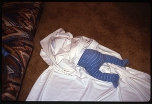 Baby lying on floor wrapped in sheet