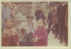 W. E. B. Du Bois sitting with two unidentified children at the Summer Palace in Beijing, China