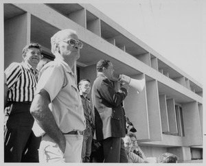 Randolph W. Bromery standing outdoors, speaking into bullhorn