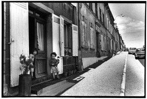 French children in front of house