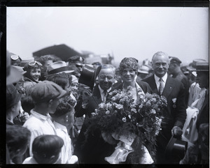 Amelia Earhart reception: Earhart with bouquet of flowers, being whisked through the crowd at the East Boston airport