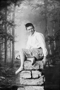 Marie Høeg Sits on a Pile of Rocks in Traditionally Men's Attire