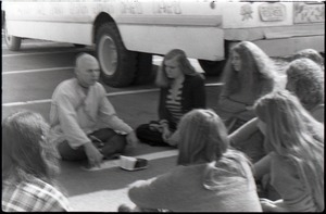 Free Spirit Press crew seated outside bus with Hare Krishna devotee