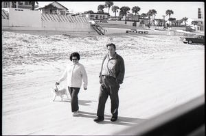 Middle-aged couple walking on beach with pet dog