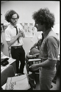 Abbie Hoffman and unidentified man looking at copy of Steal This Book