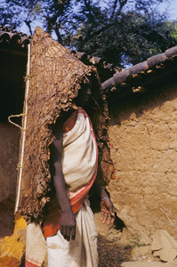 Munda woman wearing a parasol woven from leafs