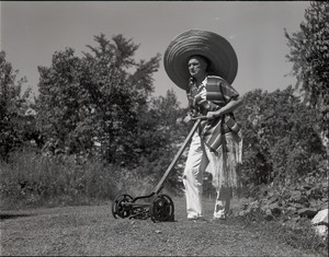 Richard Hallet, wearing sarape and sombrero, mowing the lawn