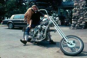 Michael Rapunzel with motorcycle, Cadillac, and admirer at the Lodge