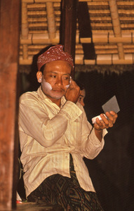 Balinese temple dancer applying his stage makeup
