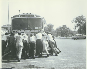 Alumni Medal recipients and family pushing a bus during Centennial Alumni weekend